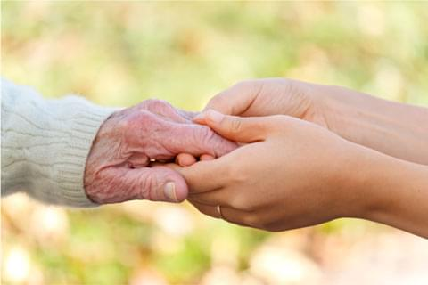 Hands holding older person's hands