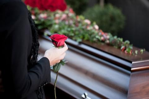 Hand holding a rose at the funeral