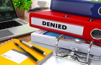 """office supplies and a red file with the """"denied"""" inscription"""